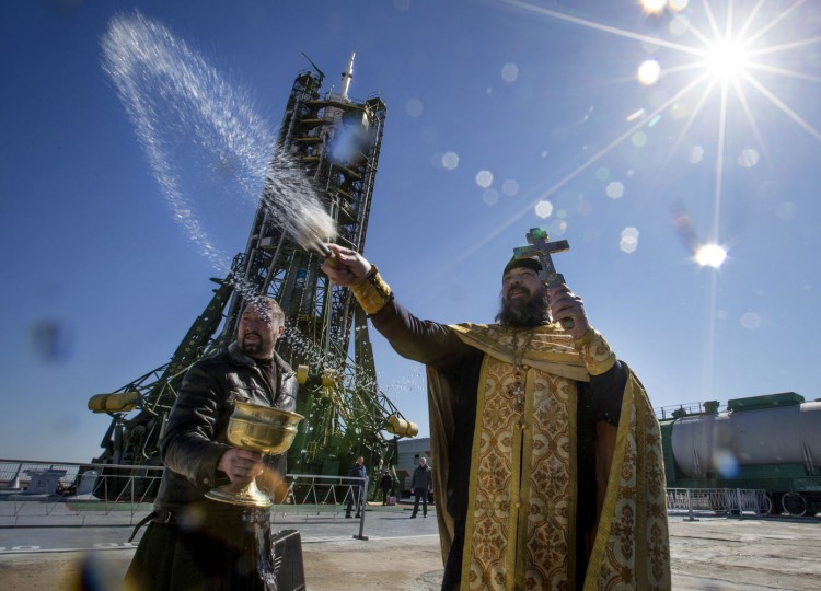 An Orthodox priest conducts a blessing service in front of the Soyuz TMA-16M spacecraft at the Russian leased Baikonur cosmodrome, Kazakhstan, Thursday, March 26, 2015. The new Soyuz mission is scheduled for Saturday, March 28. (AP Photo/Dmitry Lovetsky)