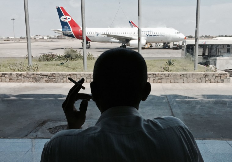 A man stranded at the Aden International Airport waits during gunbattles between a unit of police commandos loyal to longtime autocratic former President Ali Abdullah Saleh and security forces loyal to the current president in Aden, Yemen, Thursday, March 19, 2015. Forces loyal to Saleh stormed a section of the international airport in the southern port city of Aden on Thursday, triggering heavy gunbattles with security forces loyal to the current president. The fighting forced the closure of the facility and passengers on a flight to Cairo were scuttled off the plane and into the terminal building. (AP Photo/Hamza Hendawi)
