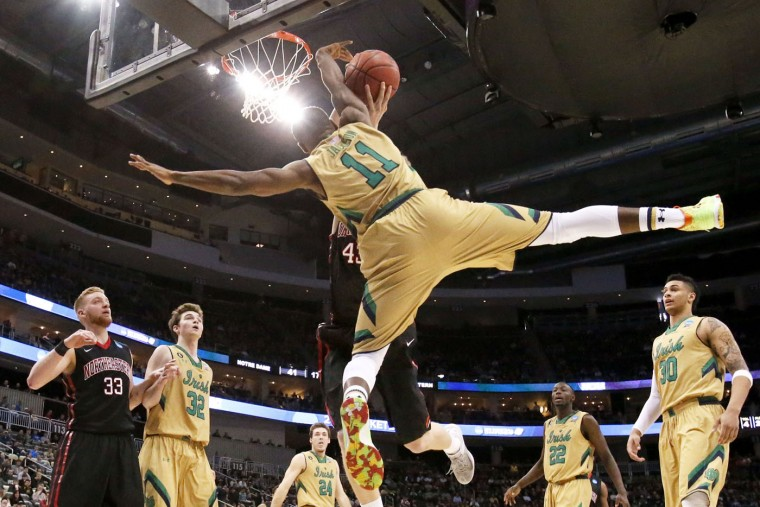 Notre Dame's Demetrius Jackson (11) tries to block a shot by Northeastern's Scott Eatherton during the second half of an NCAA tournament second round college basketball game, Thursday, March 19, 2015, in Pittsburgh. (AP Photo/Gene J. Puskar)