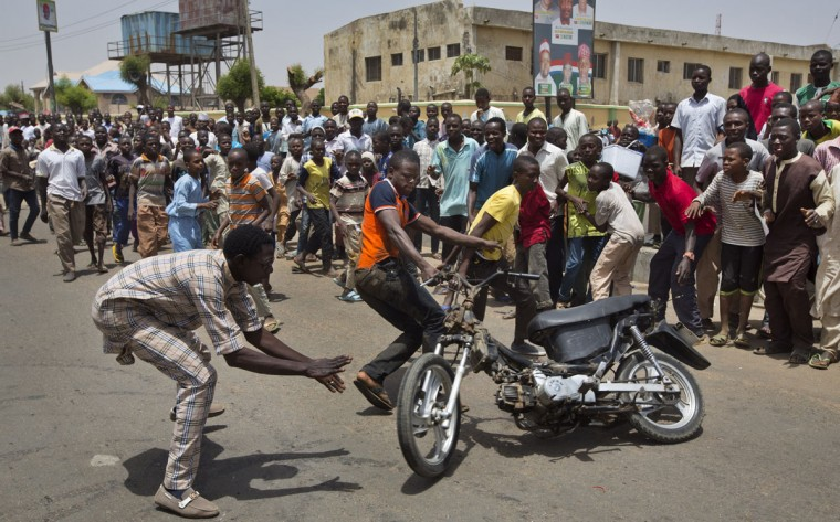 Supporters of opposition candidate Gen. Muhammadu Buhari's All Progressives Congress (APC) party celebrate by wheel-spinning motorcycles what they said was the senatorial win in Kano Central district of APC candidate Rabiu Musa Kwankwaso, in Kano, northern Nigeria Monday, March 30, 2015. Nigerians are waiting in hope and fear for results of the most tightly contested presidential election in the nation's turbulent history. (AP Photo/Ben Curtis)
