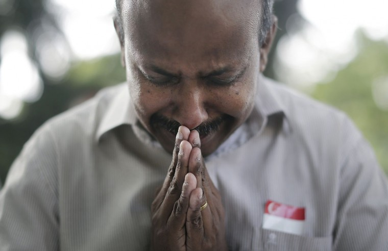 "Gunasegaran S., 51, from Singapore prays quietly outside the Istana presidential palace where boards were erected for members of the public to offer their condolences, Monday, March 23, 2015, in Singapore. Singaporeans wept and world leaders paid tribute Monday as the Southeast Asian city-state mourned the death of its founding father Lee Kuan Yew. The government announced that Lee ""passed away peacefully"" several hours before dawn at Singapore General Hospital. He was 91. (AP Photo/Wong Maye-E)"