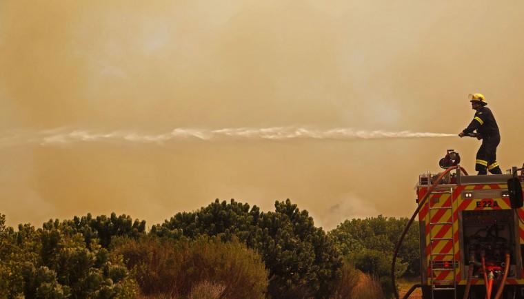 Fire fighters battle a fire near the town of Hout Bay, South Africa, Monday, March 2, 2015. (AP Photo/Schalk van Zuydam)
