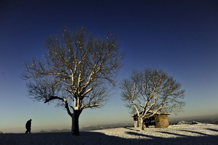 A man goes for a walk next to Aralar Sanctuary covered by snow, in Aralar, northern Spain, Monday, Feb. 9, 2015. (AP Photo/Alvaro Barrientos)