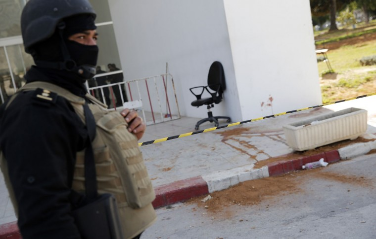 A policeman guard the entrance of the Bardo museum in Tunis, Tunisia, Thursday, March 19, 2015, as a a blood stain is seen at right, a day after gunmen opened fire killing over 20 people, mainly tourists. One of the two gunmen who killed tourists and others at a prominent Tunisian museum was known to intelligence services, Tunisia's prime minister said Thursday. But no formal links to a particular terrorist group have been established in an attack that threatens the country's fledgling democracy and struggling tourism industry. (AP Photo/Christophe Ena)