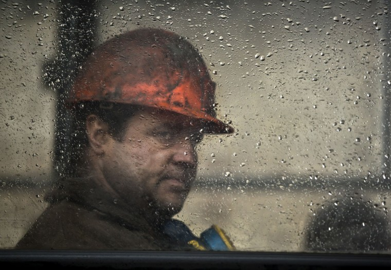 A Ukrainian coal miner sits inside a bus after exiting the underground of the Zasyadko mine in Donetsk, Ukraine, Wednesday, March 4, 2015. An explosion ripped through a coal mine before dawn Wednesday in war-torn eastern Ukraine, killing at least one miner and trapping more than 30 others underground, rebel and government officials said. (AP Photo/Vadim Ghirda)