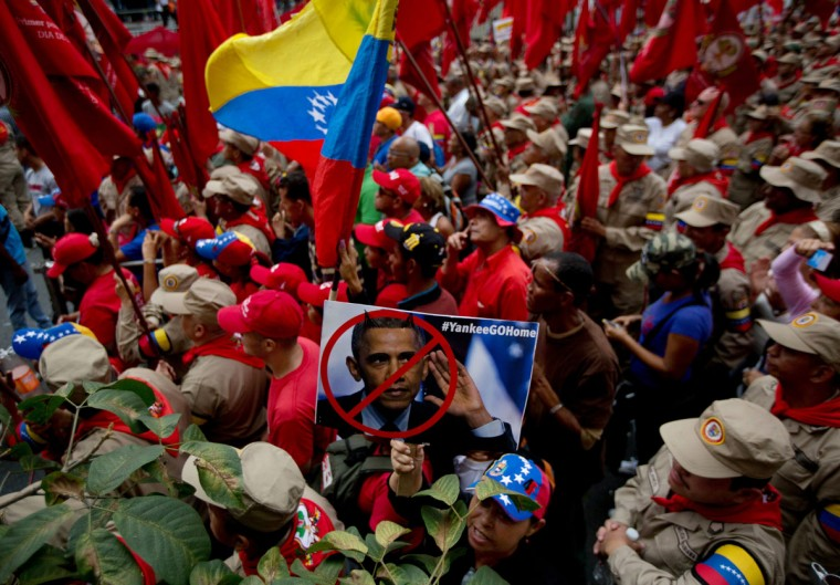 A supporter of Venezuela's President Nicolas Maduro, surrounded by uniformed members of the Bolivarian Militia, holds a defaced photograph of U.S. President Barack Obama at a pro-government rally outside Miraflores presidential palace in Caracas, Venezuela, Sunday, March 15, 2015. Venezuela's parliament approved on Sunday a law giving President Nicolas Maduro the power to legislate by decree for nine months in the face of what he describes as threats by the U.S. government. (AP Photo/Fernando Llano)