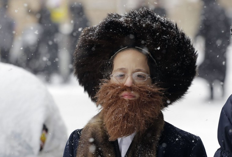 A boy wears a fake beard during a snowstorm on Purim, Thursday, March 5, 2015 in the Williamsburg neighborhood of the Brooklyn borough of New York. The day commemorates the deliverance of the Jewish people in the ancient Persian Empire. (AP Photo/Mark Lennihan)
