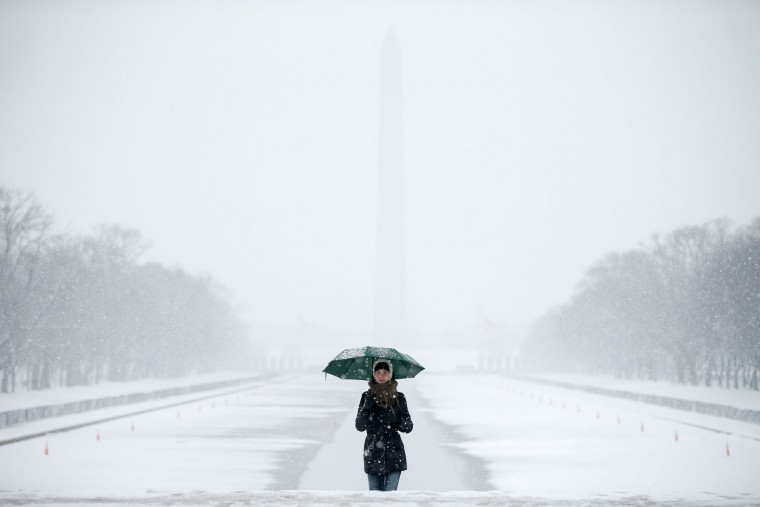 The Washington Monument and the Reflecting Pool are visible behind Claudia Marusanici, visiting from Romania, as she makes her way towards the Lincoln Memorial on the National Mall in Thursday, March 5, 2015, in the falling snow. The U.S. federal government said its offices in the Washington area will be closed Thursday because of a new round of winter weather expected in the region. The Office of Personnel Management said non-emergency personnel in and around Washington were granted excused absences for the day. Emergency employees and telework-ready employees were expected to work. (AP Photo/Andrew Harnik)