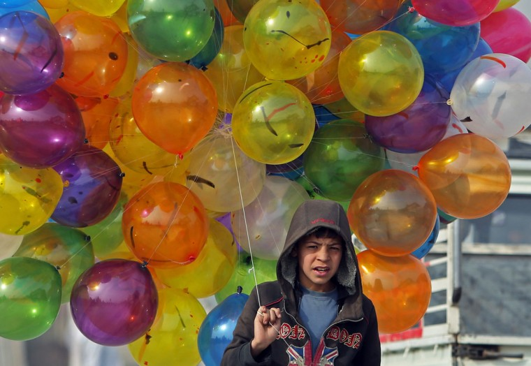An Afghan boy carries balloons for sale in Kabul, Afghanistan, Friday, Feb. 6, 2015. (AP Photo/Rahmat Gul)