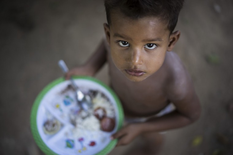 A boy looks at the camera as he eats his lunch on the shore of the polluted Jacare River in the Mandela slum of Rio de Janeiro, Brazil, Wednesday, March 4, 2015. The environmentalist and human rights organization Rio de Paz organized a press tour to the area to speak with residents who are asking the government to clean up the river and invest in recreational areas. The Jacare River flows into Guanabara Bay, where next yearís Olympic sailing events are to be held. (AP Photo/Felipe Dana)