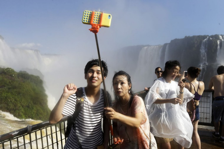 In this Saturday, March 14, 2015 photo, Japanese tourists Hiromi Kanetake, right, and her son Takayuki, photograph themselves with a phone camera as they stand in the spray on the Brazilian side of Iguazu falls, behind, in Foz do Iguazu, Brazil. Iguazu Falls is located on Brazil's border with Argentina. (AP Photo/Jorge Saenz)