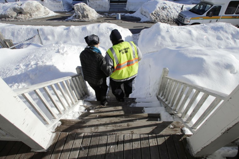 In this Tuesday March 3, 2015 photograph, Charla Nash grabs the arm of shuttle driver Roland Copeland as they walk from her front steps past five-foot high snowbanks toward a van outside her apartment in Boston. The Department of Defense is following Nash's progress, after funding her transplant surgery in 2011. Nash, who is blind, lost her face, eyes and hands after being mauled by a chimpanzee in 2009. (AP Photo/Charles Krupa)