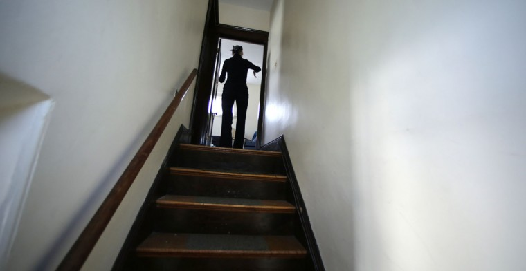 In this Friday, Feb. 20, 2015 photograph, Charla Nash climbs the stairs at her second-story apartment in Boston. Nash, who is blind with only one digit remaining on her right arm, lost her face, eyes and hands after being mauled by a chimpanzee in 2009. The military is hoping the information they learn from Nash's rehabilitation can help young, seriously disfigured soldiers returning from war. (AP Photo/Charles Krupa)