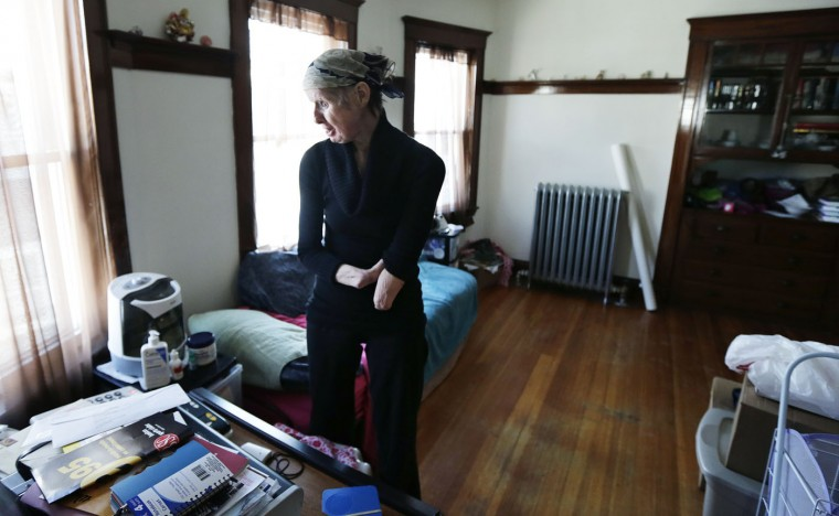 In this Friday, Feb. 20, 2015 photograph, Charla Nash chats with a neighbor on the speakerphone in her bedroom at her second-story apartment in Boston. The Department of Defense is following Nash's progress, after funding her full-face transplant surgery in 2011. (AP Photo/Charles Krupa)