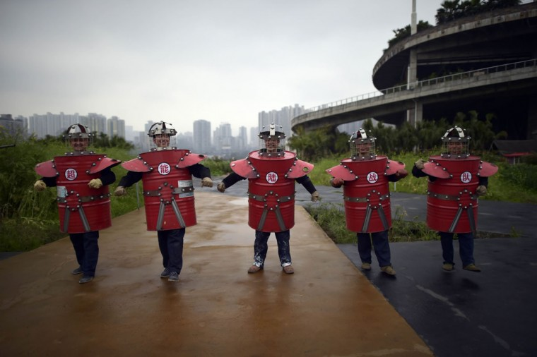 In this Thursday, March 19, 2015 photo, workers in outfits made from scrap material parade through a farm on the rooftop of a door manufacturer in Chongqing municipality in southwest China. Employees of the company designed and modeled their garments as part of an environmental sustainability-themed fashion show, which was held by the firm as a morale-booster for employees. (AP Photo)