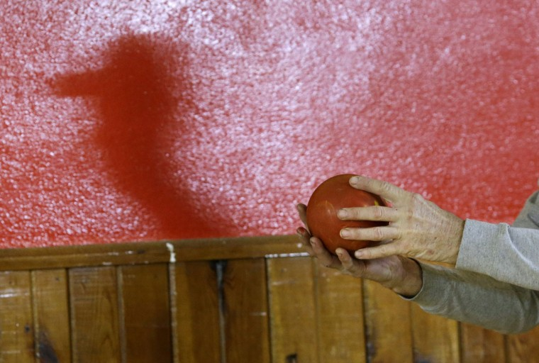 Jerry Middleton casts a shadow on a wall as he prepares to bowl a duckpin bowling ball during a tournament at Shenandoah Bowling Lanes, Saturday, March 28, 2015, in Mount Jackson, Va. Shenandoah, open since 1948, is one of around 60 remaining duckpin alleys in the United States. (AP Photo/Patrick Semansky)