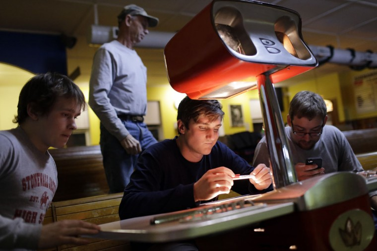 Scott Asbell, center, tallies up the score during a duckpin bowling tournament at Shenandoah Bowling Lanes, Saturday, March 28, 2015, in Mount Jackson, Va. Shenandoah, open since 1948, is one of around 60 remaining duckpin alleys in the United States. (AP Photo/Patrick Semansky)