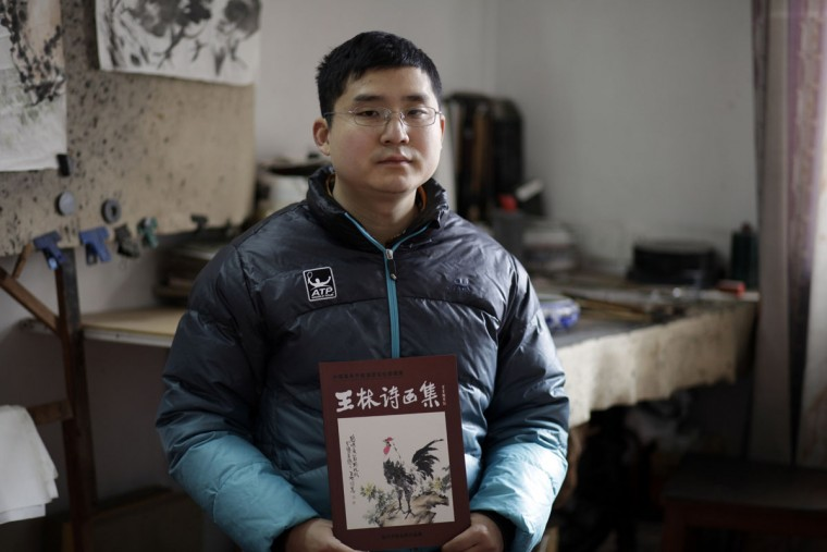 Wang Zheng holds a collection of works by his father Wang Linshi, who was onboard the missing Malaysia Airlines Flight 370, at an apartment in Nanjing in eastern China's Jiangsu province. For the past year, Wang Zheng has been avoiding one place: the modest apartment where his parents had been living for more 20 years until they vanished along with the ill-fated flight. Scrolls of paintings by his father are in piles in the living room, the guest bedroom, and the studio. Wang Zheng, the only son of Wang Linshi and Xiong Deming, said he only comes into the apartment in this eastern Chinese city when absolutely necessary. (AP Photo/Peng Peng)