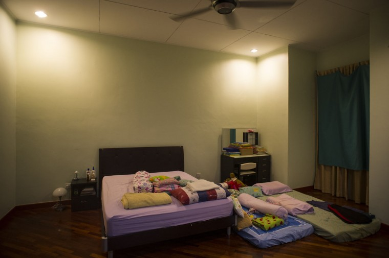 """The master bedroom of Foong Wai Yueng, 40, a stewardess who was aboard Malaysian Airlines flight 370 when it disappeared last March, in Kuala Lumpur, Malaysia. Yueng's husband, Lee Khim Fatt, 45, says """"I have not changed or moved anything except changing the sheets, as the kids have always slept with us here. But ever since that day, I sleep on the floor mattress with my son. It doesn't feel the same, doesn't feel right sleeping on the mattress without her beside me."""" (AP Photo/Joshua Paul)"""