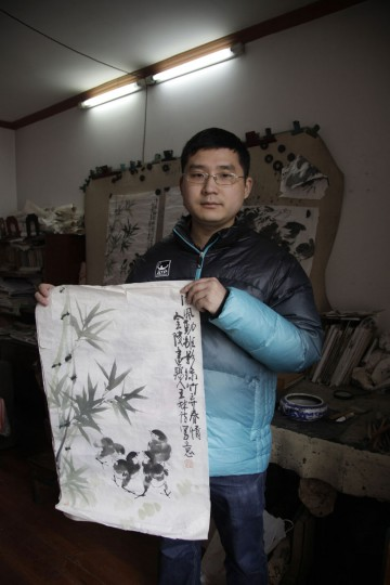 Wang Zheng holds an ink painting and calligraphy by his father Wang Linshi who was onboard the missing Malaysia Airlines Flight 370, at an apartment in Nanjing in eastern China's Jiangsu province. For the past year, Wang Zheng has been avoiding one place: the modest apartment where his parents had been living for more 20 years until they vanished along with the ill-fated flight. Scrolls of paintings by his father are in piles in the living room, the guest bedroom, and the studio. Wang Zheng, the only son of Wang Linshi and Xiong Deming, said he only comes into the apartment in this eastern Chinese city when absolutely necessary. (AP Photo/Peng Peng)