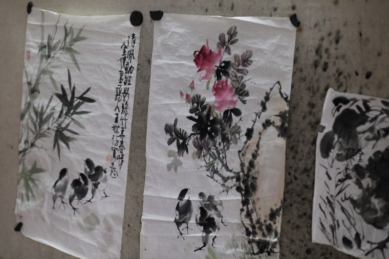 Ink paintings and calligraphy belonging to Wang Linshi, a Chinese artist who was onboard the missing Malaysia Airlines Flight 370, hang at an apartment in Nanjing in eastern China's Jiangsu province. Scrolls of paintings by Wang are in piles in the living room, the guest bedroom, and the studio. Paintbrushes - their heads long dry - hang from a workstation in a row. In the kitchen, the floor and stove have collected a thin layer of dust. (AP Photo/Peng Peng)