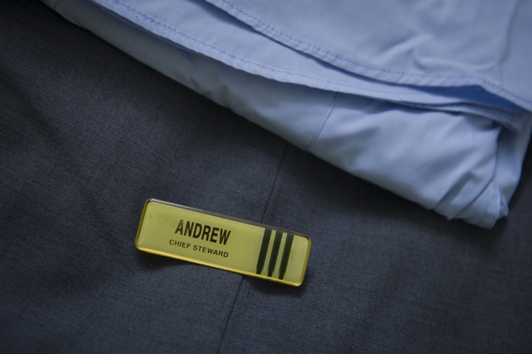 A spare name tag of Andrew Nari's is placed onto his uniform in his house outside Kuala Lumpur, Malaysia. Nari who was married to Melanie Antonio, 46, and had two children, Maira Elizabeth Nari, 19, and Malcomn Radeng Nari, 14, was the Chief Steward aboard flight 370, which disappeared March 8, 2014, while flying from Kuala Lumpur to Beijing. (AP Photo/Joshua Paul)