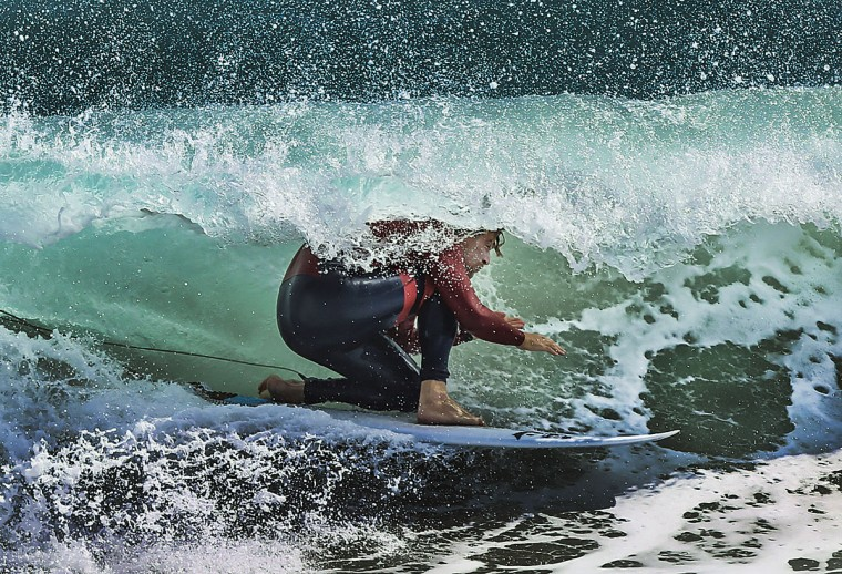 Cheyne Cottrell kneels down to surf a narrow tube formed by a wave in Palm Beach, Fla., Thursday, Feb. 19, 2015. Scores of surfers were taking advantage of the high waves that accompanied the areas low temperatures and high gusts. (AP Photo/ The Palm Beach Post, Damon Higgins)