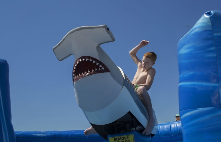 Avery Tomlinson, 13, who is from Washington Township, New Jersey, hangs on tight to Bucky the Shark outside of the Tradewinds Island Grand resort on St. Pete Beach, Fla., Monday, March 30, 2015.(AP Photo/Tampa Bay Times, John Pendygraft)