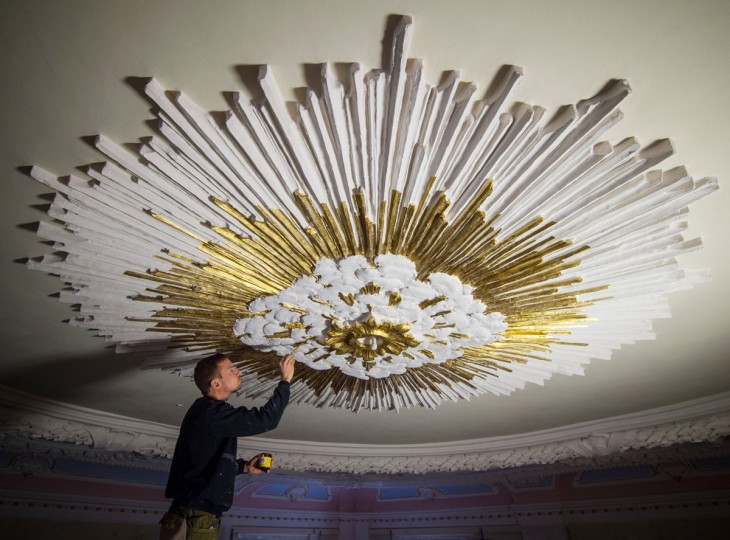 Restorer Andre Baer paints the stucco work on the ceiling of the palace chapel with bronze paint in Altlandsberg, Germany, Friday, March 6, 2015. The historic building, which has been under the ownership of the city since 2008, is currently being refurbished and is one of the few remaining examples of the Baroque style in Brandenburg. The chapel was built at the end of the 17th century and in 1786 it was rebuilt following a palace fire. The extensive renovations began in May 2013, and the building is intended to become a multifunctional convention and event center. (AP Photo/dpa, Patrick Pleul)