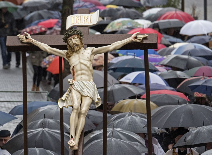 Believers carry a cross during heavy rain at the Palm Sunday procession in the old town of Heiligenstadt, central Germany, Sunday, March 29, 2015. The procession takes place with life-size figures from the Passion of Christ and under the presence of several thousand people. (AP Photo/Jens Meyer)