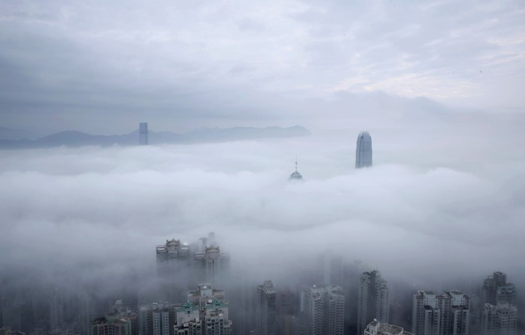 Two International Finance Centre tower, center right, and International Commerce Centre, top left, are seen over the clouds in Hong Kong, Sunday, Feb. 22, 2015. (AP Photo/Kin Cheung)