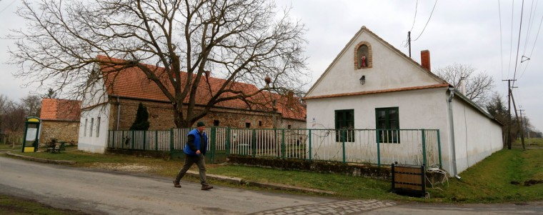 A man walks on one of the four streets in the village of Megyer, Hungary, Friday, March 13, 2015. For 210,000 forints (US Dollar 730) a day, visitors get access to seven guest houses that sleep 39 people, a bus stop, horses, chickens and four hectares (10 acres) of farm land. (AP Photo/Ronald Zak)