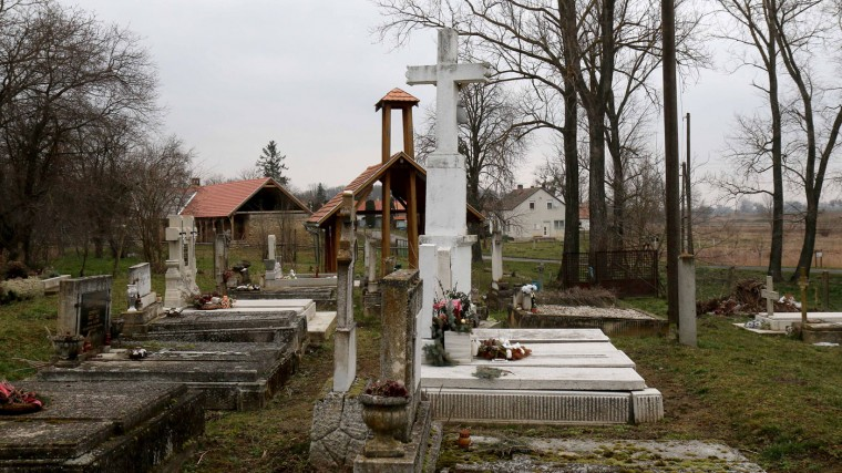 The cemetery of the village Megyer, Hungary, photographed Friday, March 13, 2015. For 210,000 forints (US Dollar 730) a day, visitors get access to seven guest houses that sleep 39 people, a bus stop, horses, chickens and four hectares (10 acres) of farm land. (AP Photo/Ronald Zak)