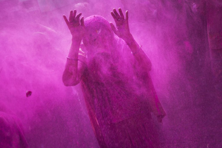 A widow raises her hands as others throw colored powder on her during celebrations marking Holi at the Meera Sahabhagini Widow Ashram in Vrindavan, India, Tuesday, March 3, 2015. The widows, many of whom at times have lived desperate lives in the streets of the temple town, celebrated the Hindu festival of colors at the ashram. (AP Photo/Bernat Armangue)