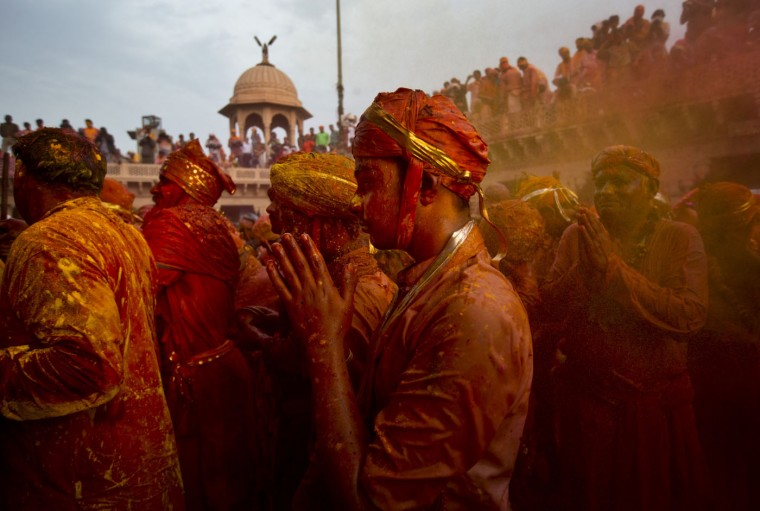 Indian Hindu devotees from Barsana village, smeared in colored powder, pray at the Nandagram Temple, famous for Lord Krishna and his brother Balram, during Lathmar holi festival, in Nandgaon, India, Saturday, Feb. 28, 2015. During Lathmar Holi the women of Nandgaon, the hometown of Krishna, beat the men from Barsana, the legendary hometown of Radha, consort of Hindu God Krishna, with wooden sticks in response to their teasing as they depart the town. (AP Photo/Saurabh Das)