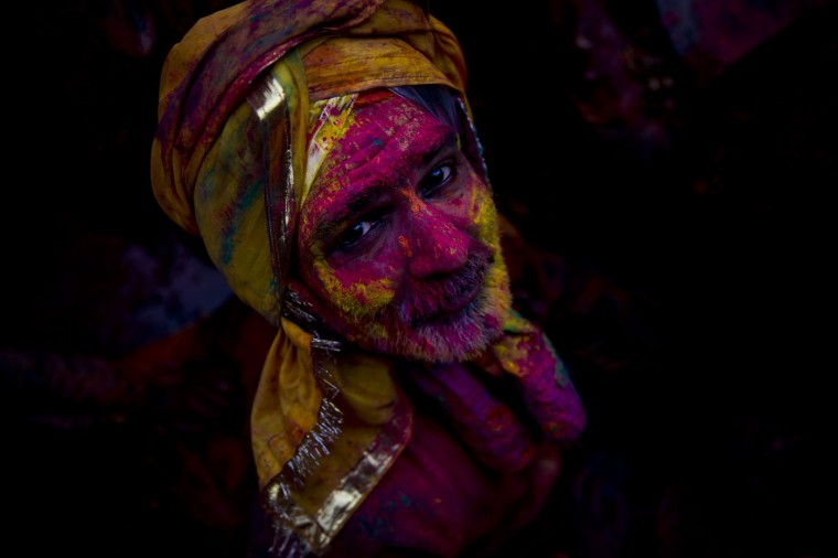 A Hindu devotee smeared with colors watches as he visits the Nandagram temple, famous for Lord Krishna and his brother Balram, during Lathmar holi festival, in Nandgaon, India, Saturday, Feb. 28, 2015. During Lathmar Holi the women of Nandgaon, the hometown of Krishna, beat the men from Barsana, the legendary hometown of Radha, consort of Hindu God Krishna, with wooden sticks in response to their teasing as they depart the town. (AP Photo/Saurabh Das)