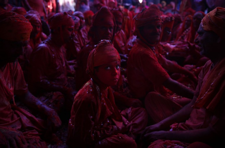 An Indian Hindu boy from the village of Nandgaon sits with others at the Ladali or Radha temple before taking out a procession for the Lathmar Holi festival, at the legendary hometown of Radha, consort of Hindu God Krishna, in Barsana, 115 kilometers (71 miles) from New Delhi, India, Friday, Feb. 27, 2015. During Lathmar Holi the women of Barsana beat the men from Nandgaon, the hometown of Lord Krishna, with wooden sticks in response to their teasing. (AP Photo/Saurabh Das)