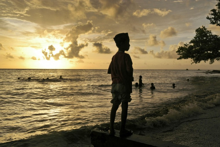 A Muslim boy stands on Kastela Beach during sunset in Ternate, North Maluku, Indonesia, Friday, March 6, 2015. (AP Photo/Dita Alangkara)