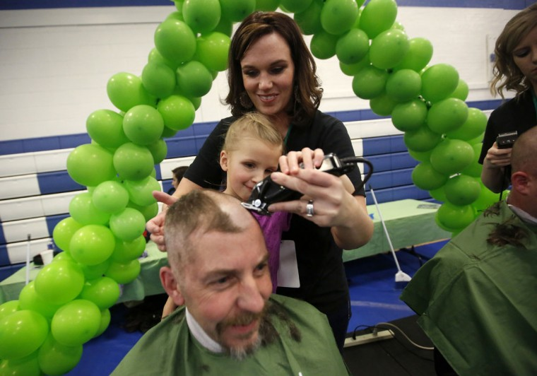 Katie Jordan, instructor at Capri College, assists cancer survivor Jordyn Gourley, 7, as they shave the head of Brian Miller, during the St. Baldrick's Foundation fundraiser at the University of Dubuque, in Dubuque, Iowa, on Thursday, March 26, 2015. (AP Photo/Telegraph Herald, Mike Burley)