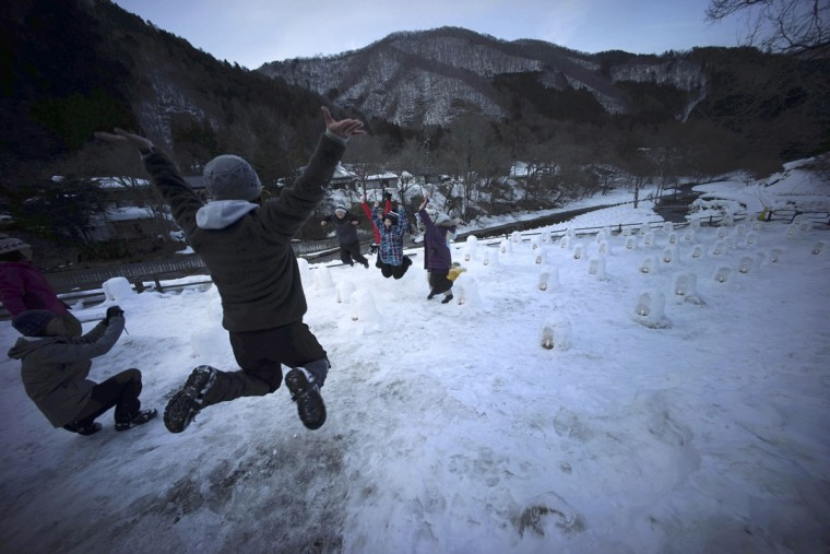 Volunteers jump as they take a photograph near snow-made small igloos illuminating at the Yunishigawa Kamakura Festival in Yunishigawa, Tochigi prefecture, north of Tokyo, Saturday, Feb. 7, 2015. (AP Photo/Eugene Hoshiko)