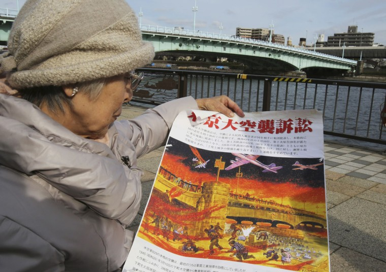 Michiko Kiyo-oka, 91, holds a banner read as Tokyo Firebombing lawsuit at the riverside of Sumida river near the Asakusa district in Tokyo. Kiyo-oka, a city government worker and daughter of traditional entertainers, ran with her parents and sister toward the Sumida river, crowding with many others under the Kototoi Bridge. Kiyo-oka managed to avoid being pushed into the deep water, and her mother also survived at the waterís edge. But her sister swam for a wooden post that caught fire and her father died trying to save her. Hundreds of people drowned, suffocated or were burned to death as the waterís surface, slick with napalm, caught fire. (AP Photo/Koji Sasahara)