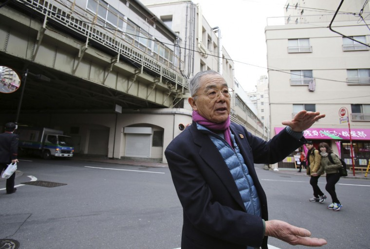 Yoshitaka Kimura speaks near Asakusa Station in Tokyo. Kimura, sixth generation heir to the familyís toy business, was just seven when his family fled during the firebombing from their shop near Asakusaís famous Sensoji Temple, heading toward the Sumida River. The blast from a falling bomb blew him under the half-closed shutter of the Matsuya department store, one of the few buildings left standing after the attack. He and others crowded inside survived. (AP Photo/Koji Sasahara)