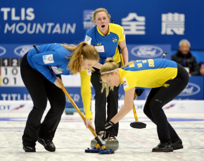 Sweden's Maria Prytz, center, yells out to sweepers after releasing the rock as the team plays Norway during the fourth end in the women's World Curling Championships in Sapporo, northern Japan, Tuesday, March 17, 2015. (AP Photo/Kyodo News, Ryosuke Uematsu)