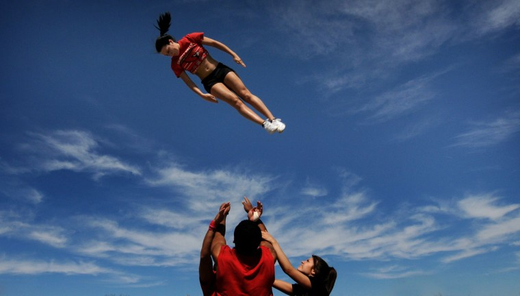 Members of the Trinity Valley Community College cheer team, from Athens, Texas, practice Friday afternoon March 20, 2015, in a park in Salina, Kan. They will be cheering their team on through Saturday at the NJCAA Women's Championship tournament in Salina. (AP Photo/Salina Journal, Tom Dorsey)