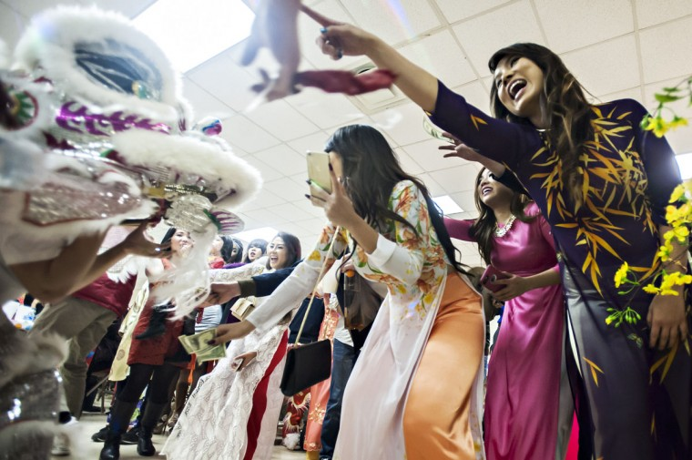 People react to a dragon dance Sunday, Feb. 22, 2015, during a Vietnamese New Year celebration at the Jaycee Pavilion in Lampkin Park in Bowling Green, Ky. (AP Photo/Daily News, Bac Totrong)