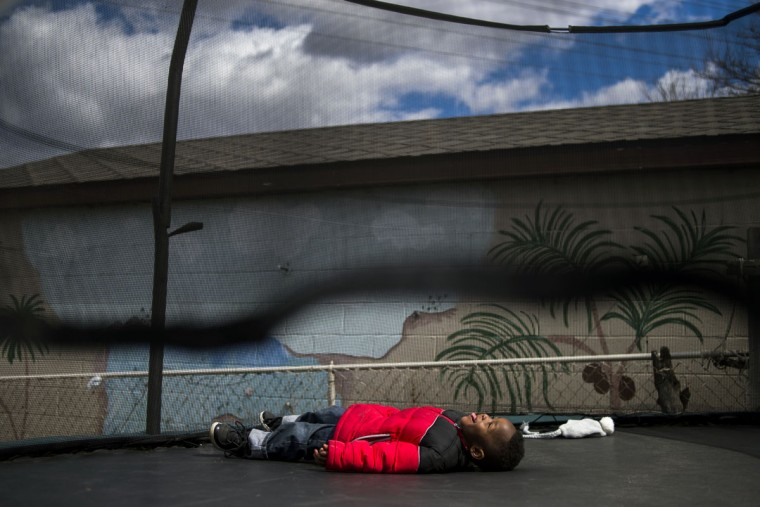 Jeremiah Smith, 3, of Flint sticks his tongue out amidst while laying on his back to look up at the clouds after tuckering out from jumping on a trampoline, Monday, March 30, 2015 in a neighbor's backyard on Flint's south side. (AP Photo/The Flint Journal, Jake May)