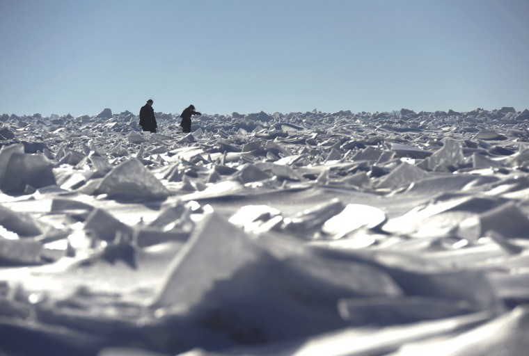 Two women navigate their way among mounds of frozen ice on Lake Michigan in South Haven, Mich., Sunday, March 8, 2015. (AP Photo/The Herald-Palladium, Don Campbell)