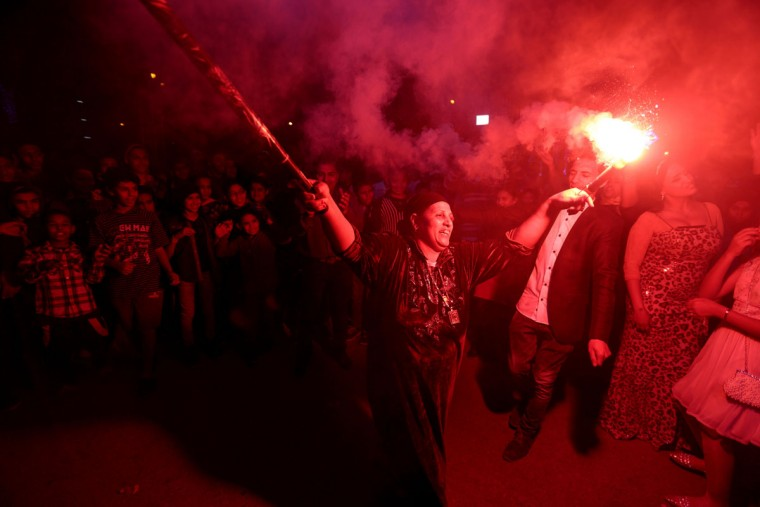 "In this Thursday, March 5, 2015 photo, a woman dances with flares during a local wedding in Salam City, a suburb on the outskirts of Cairo. Since the 2011 uprising, the music of ""Mahraganat,"" Arabic for ""festivals,"" has emerged from and spread through impoverished communities, where local musicians play, especially during weddings, their auto-tuned beats and songs that tackle social, political and cultural issues. (AP Photo/Mosa'ab Elshamy)"