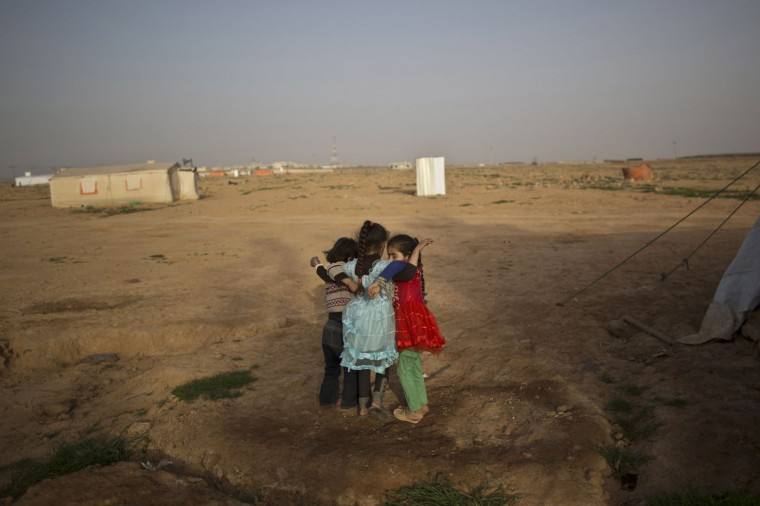 In this Saturday, March 7, 2015 photo, Syrian refugee girls walk while holding onto each other at an informal tented settlement on the outskirts of Mafraq, Jordan. In June 2014, a survey commissioned by UNICEF said there were 125 informal tent settlements for Syrian refugees across Jordan, home to some 10,000 people. The survey said nearly 80 percent there were younger than 18. (AP Photo/Muhammed Muheisen)