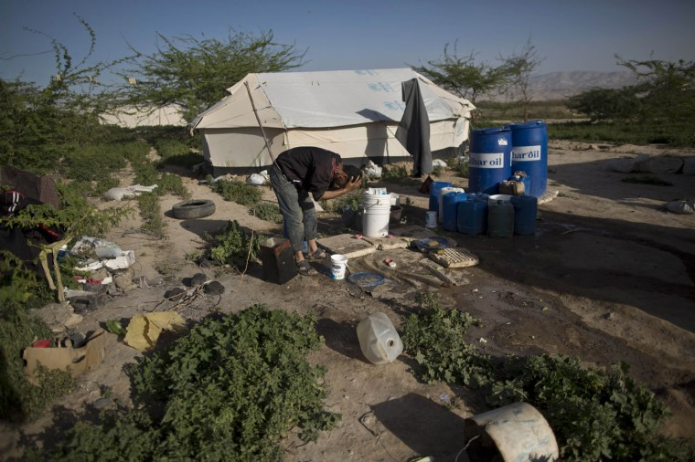 In this Friday, March 6, 2015 photo, a Syrian refugee bathes at an informal tented settlement in the Jordan Valley, Jordan. Aid officials say those in the makeshift camps are among the most vulnerable of close to 625,000 Syrians who fled to Jordan and have registered with the U.N. refugee agency. (AP Photo/Muhammed Muheisen)
